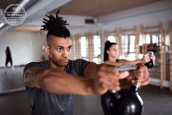 A man and a woman doing crossfit with a kettlebell