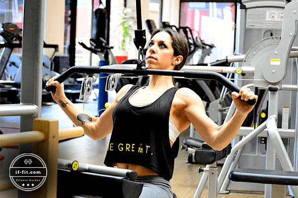 A woman using a lat pulldown machine on a gym