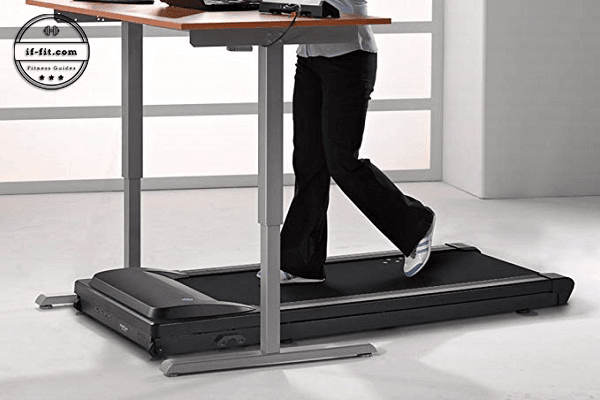 A woman using an under desk treadmill